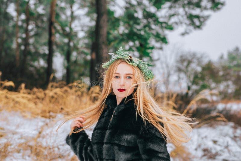 Het portret van het meisje in een kroon van pijnboomnaalden met hun lang blondehaar is de boseffect retro foto, korrel stock fotografie