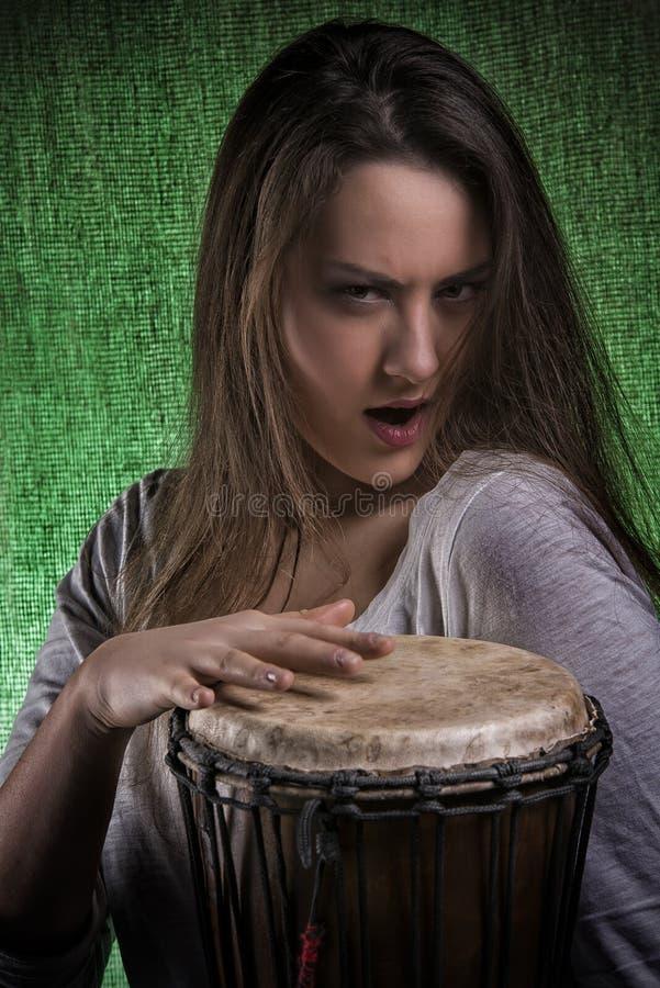 Expressieve Wilde Vrouw die Trommel Djembe spelen royalty-vrije stock foto