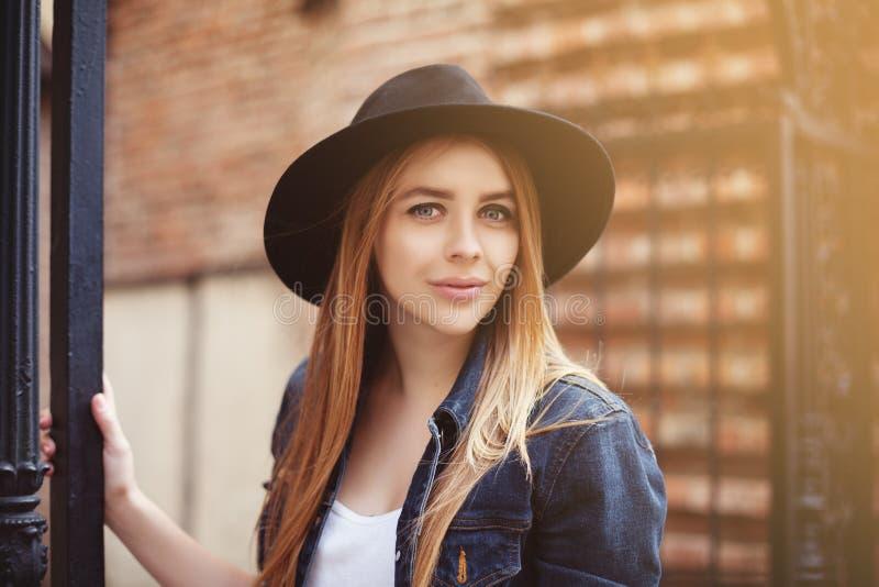 Het portret van het mooie modieuze meisje modieus dragen breed-brimmed zwarte hoed bekijkend camera De Levensstijl van de stad sl royalty-vrije stock foto