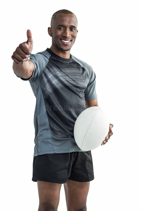 Het portret van het zekere rugbyspeler glimlachen en het tonen beduimelt omhoog stock foto's