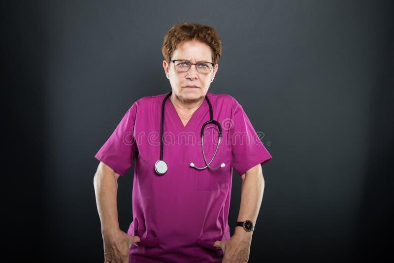 Het portret van hogere dame arts boos met dient zakken in stock foto