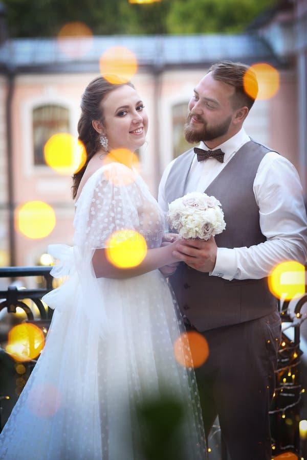 Het portret van het huwelijkspaar in de restaurantyard met slingerslichten