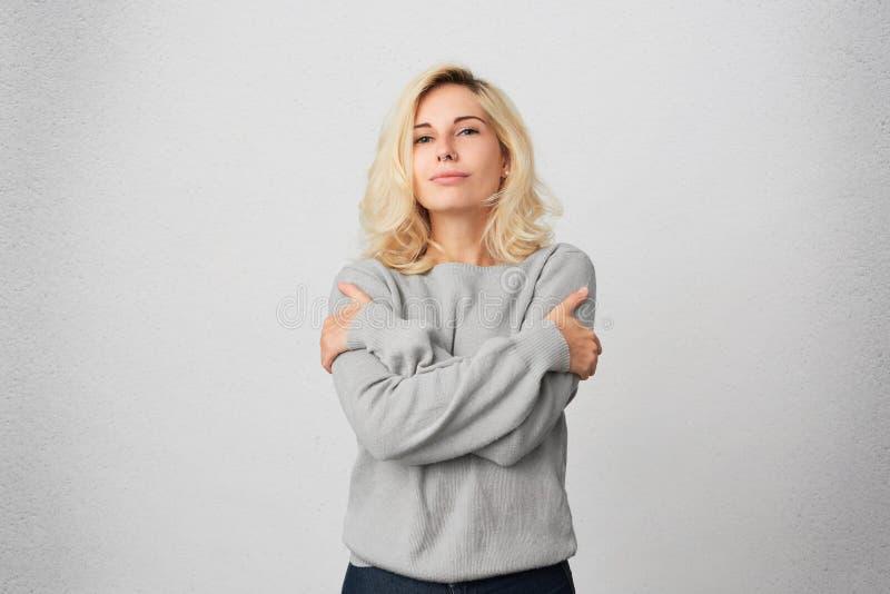 Het portret van jong blondemeisje omhelst zich, draagt toevallige grijze sweater en voelt comfortabel en warm stock afbeelding