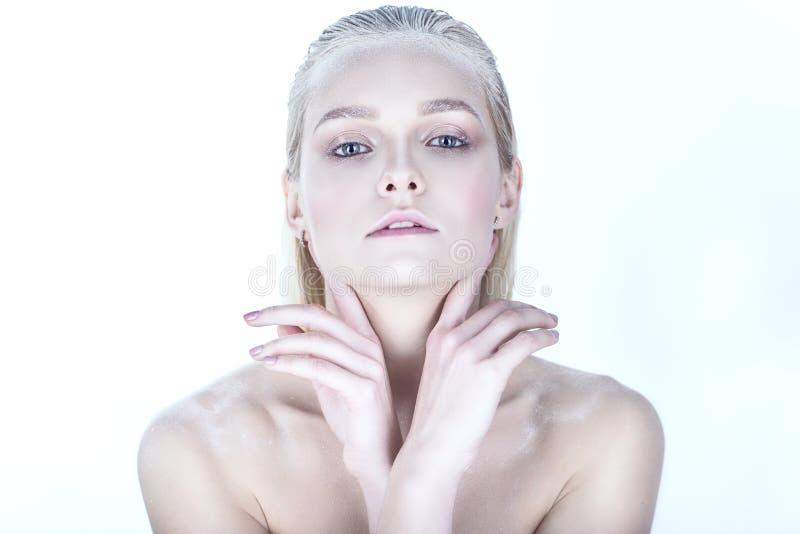 Het portret van jong mooi blond model met naakt maakt omhoog, slicked achterhaar en naakte schouders houdend haar die handen bij  royalty-vrije stock fotografie