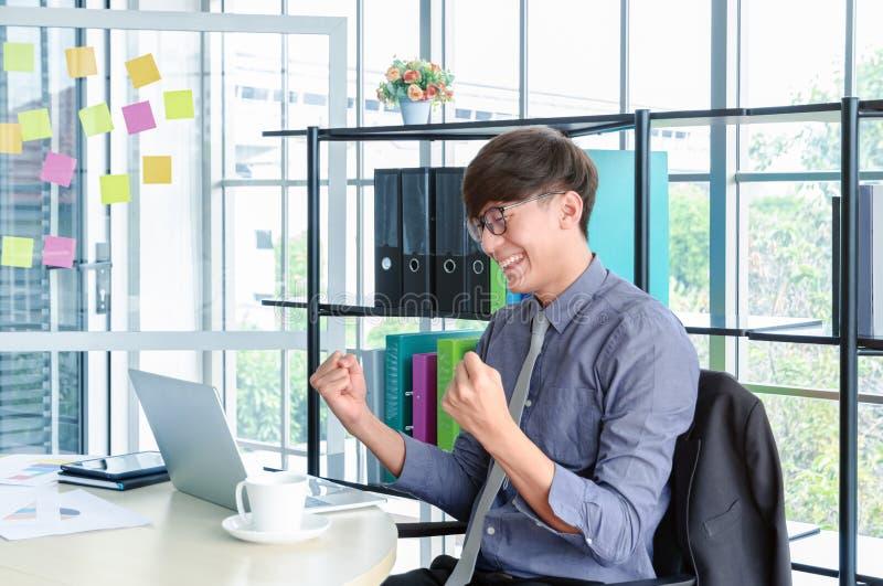 Het portret van jonge Aziatische zegevierend zakenman en viert met wapens omhoog voor baansucces in bureau royalty-vrije stock foto