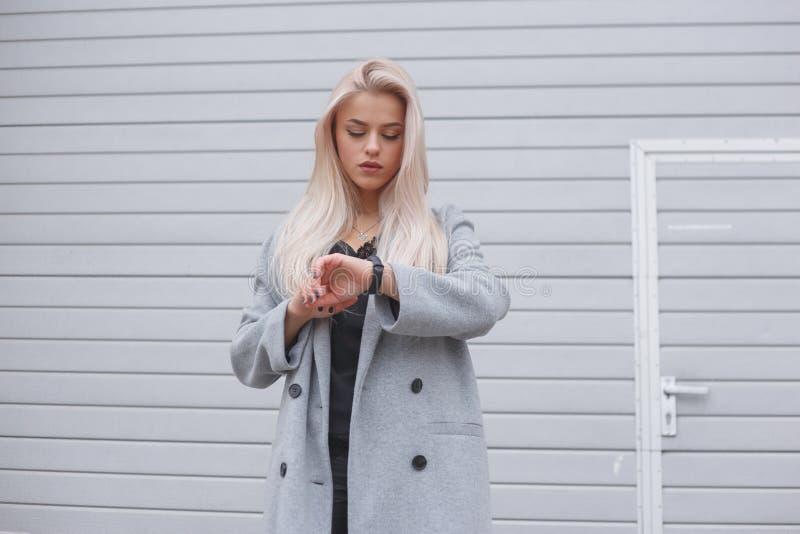 Het portret van jonge blondhair kleedde elegant vrouw in een laag gebruikt een slimme armband die zich in openlucht bevinden stock foto's
