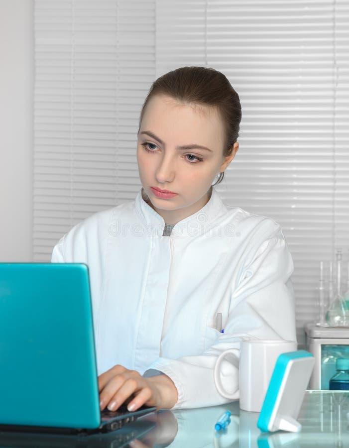 Het portret van jonge dokter of de wetenschapper die aan draagbaar werken verwerkt gegevens royalty-vrije stock afbeelding