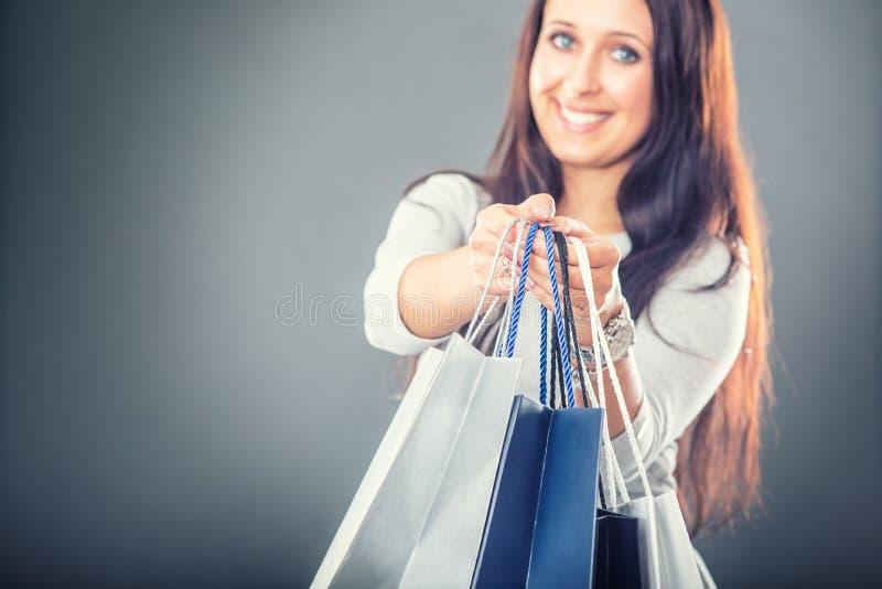 Het portret van jonge gelukkige glimlachende vrouw met het winkelen doet creditcard en schoenen in zakken royalty-vrije stock foto's