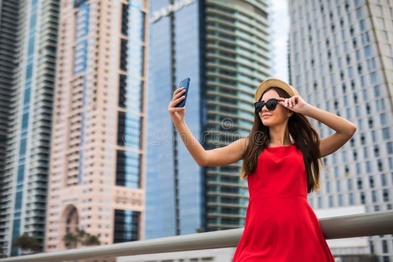 Het portret van jonge glimlachvrouw in rode kleding, de zonnebril en de de zomerhoed maken selfie of videogesprek op de telefoon  stock foto