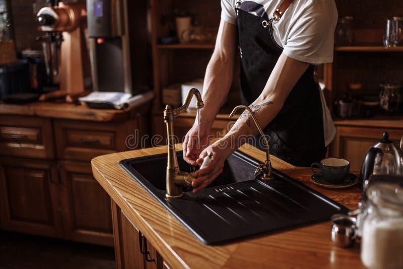 Het portret van jonge kelner die van hem wassen dient keuken bij koffie in royalty-vrije stock foto