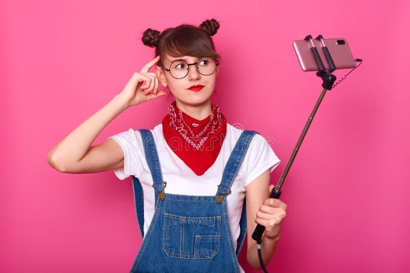 Het portret van jonge magnetische knappe vrouwelijke holding selfie plakt met hand, wat betreft hoofd, bekijkend camera, makend f stock afbeeldingen
