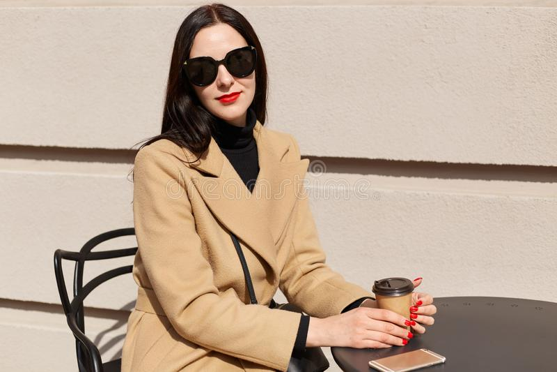Het portret van jonge mooie donkerbruine vrouw in modieuze zonnebril en beige modieuze laag zit bij lijst in openluchtkoffie royalty-vrije stock afbeelding