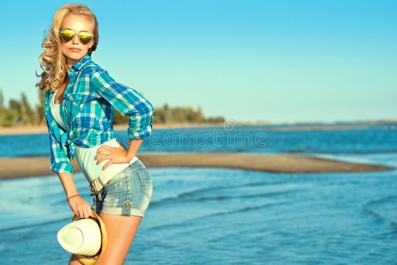 Het portret van jonge schitterende sexy suntanned blonde dragende weerspiegelde hart gevormde zonnebril die zich bij de kustholdi stock foto's
