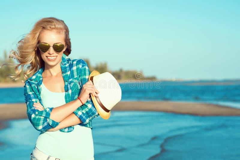 Het portret van jonge schitterende sexy suntanned blonde dragende weerspiegelde hart gevormde zonnebril en controleerde blauw ove stock afbeelding