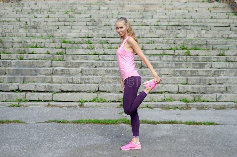 Het portret van jonge sportieve vrouw in sportkleding doet uitrekkende oefeningen openlucht stock afbeeldingen