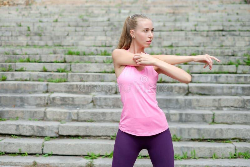 Het portret van jonge sportieve vrouw in sportkleding doet uitrekkende oefeningen openlucht stock afbeelding