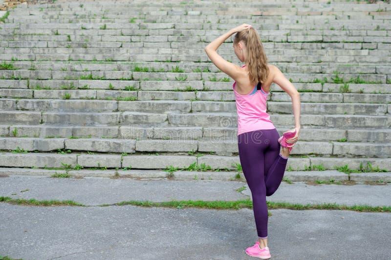 Het portret van jonge sportieve vrouw in sportkleding doet uitrekkende oefeningen openlucht royalty-vrije stock fotografie