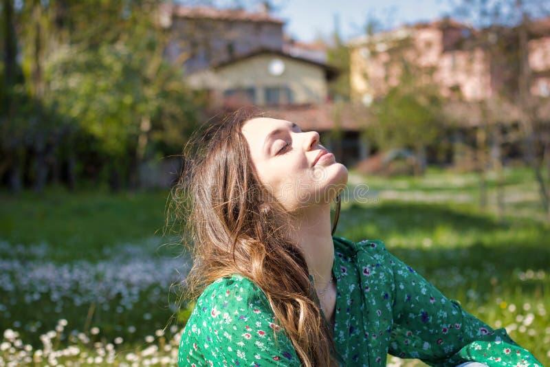 Het portret van jonge vrouw met zuivere huidzitting ontspant binnen op een gebied royalty-vrije stock afbeelding