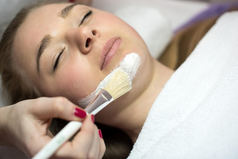 Het portret van jonge vrouw terwijl het hebben van gezichtsmasker is door beauti van toepassing stock afbeelding