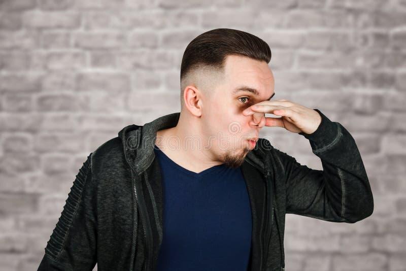 Het portret van Kaukasische kerel, dichte neus, stinkt Mens op bakstenen muurachtergrond stock afbeeldingen
