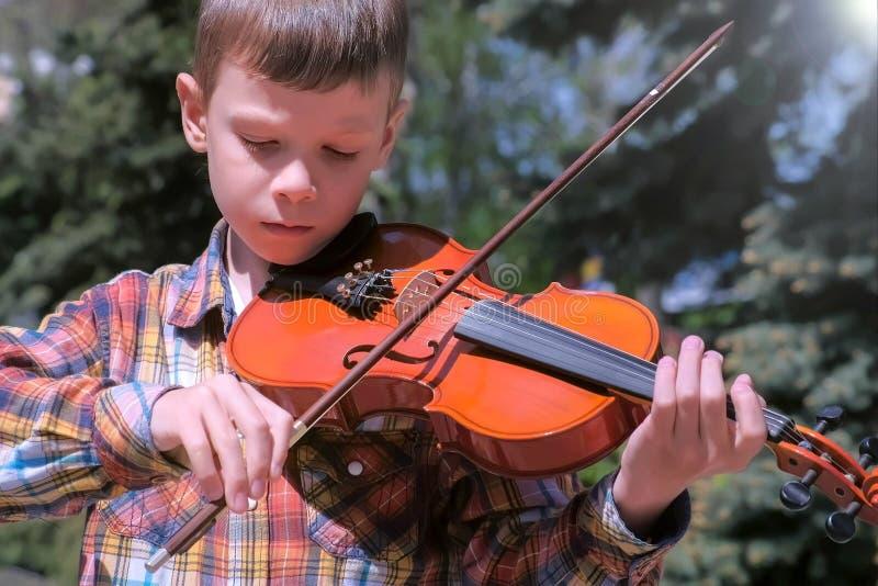 Het portret van kindjongen speelt de viool die zich in park op pijnboomachtergrond bevinden royalty-vrije stock afbeelding