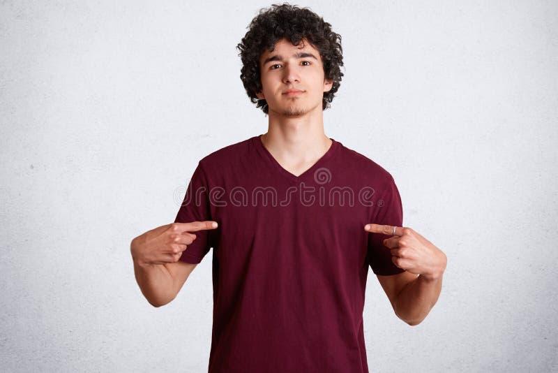 Het portret van knap jong mannetje wijst op bij lege ruimte van toevallige t-shirt voor uw reclame of ontwerpend inhoud, heeft ch royalty-vrije stock fotografie