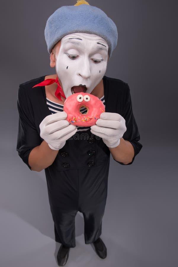 Het portret van knap mannetje bootst het eten van een smakelijk roze na stock afbeeldingen