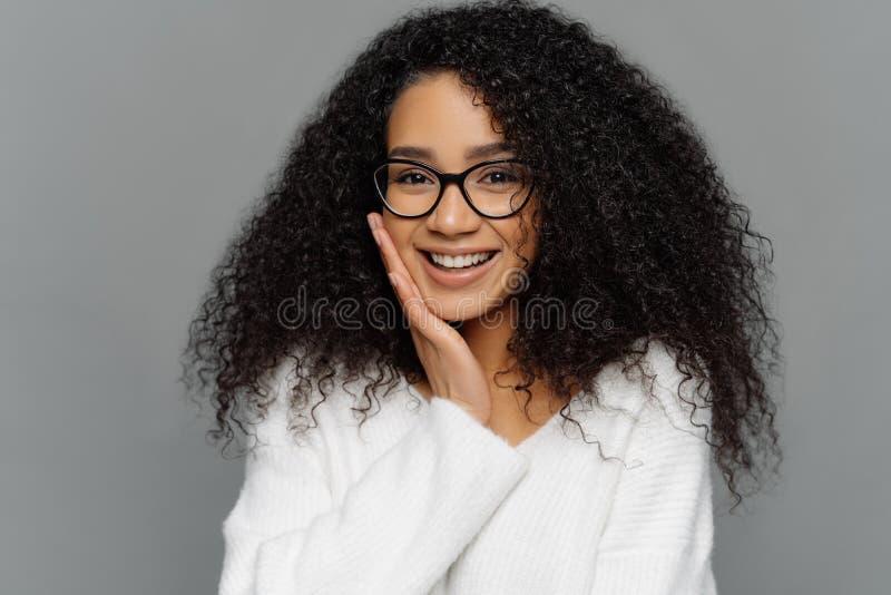 Het portret van knappe Afro-vrouw raakt wang, gelukkig glimlacht, geniet van ontvangend compliment, voelt schuw, gekleed in witte royalty-vrije stock foto