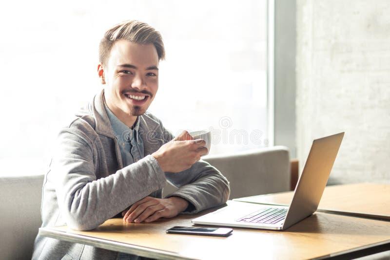 Het portret van knappe gelukkige gebaarde jonge zakenman in grijze blazer zit in koffie en heeft een onderbreking met kop van kof royalty-vrije stock fotografie