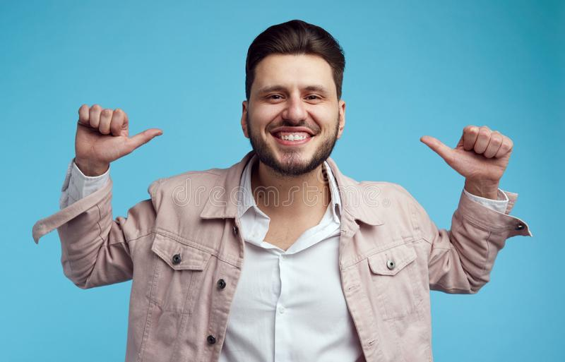 Het portret van knappe Kaukasische mannelijke punten met beide duimen bij zich, heeft brede glimlach, die zich tegen blauw bevind royalty-vrije stock foto's