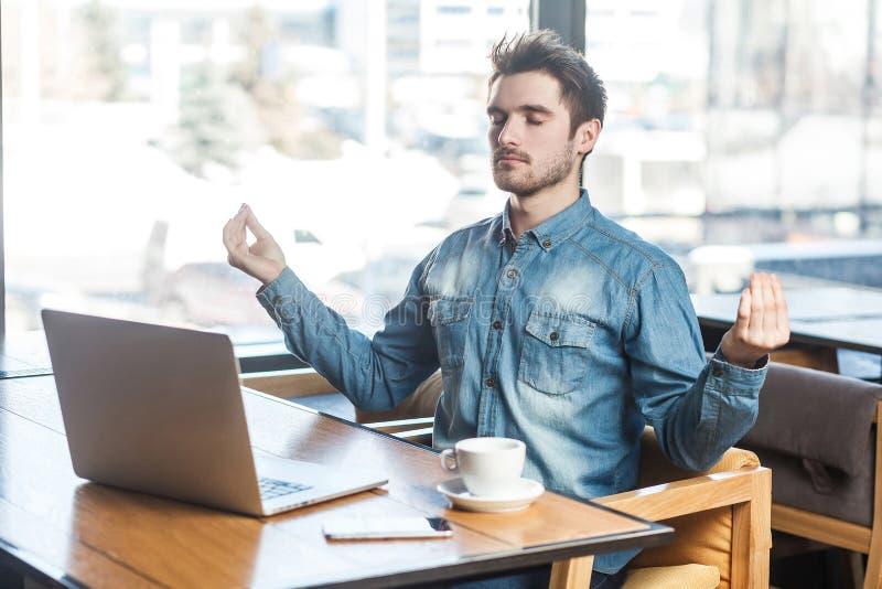 Het portret van knappe succesvolle gebaarde jonge freelancer in jeansoverhemd zit in koffie en heeft een rust, die handen houden stock foto's