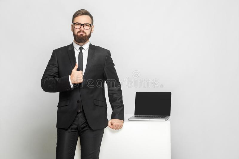 Het portret van knappe zekere succesvolle gebaarde jonge zakenman in intelligentie zwart kostuum bevindt zich dichtbij zijn werke stock foto