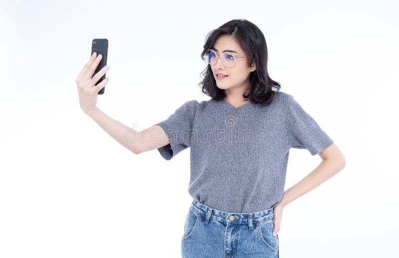 Het portret van koel vrolijk Aziatisch meisje met oogglazen neemt een selfie door haar die smartphone op een witte achtergrond wo royalty-vrije stock foto