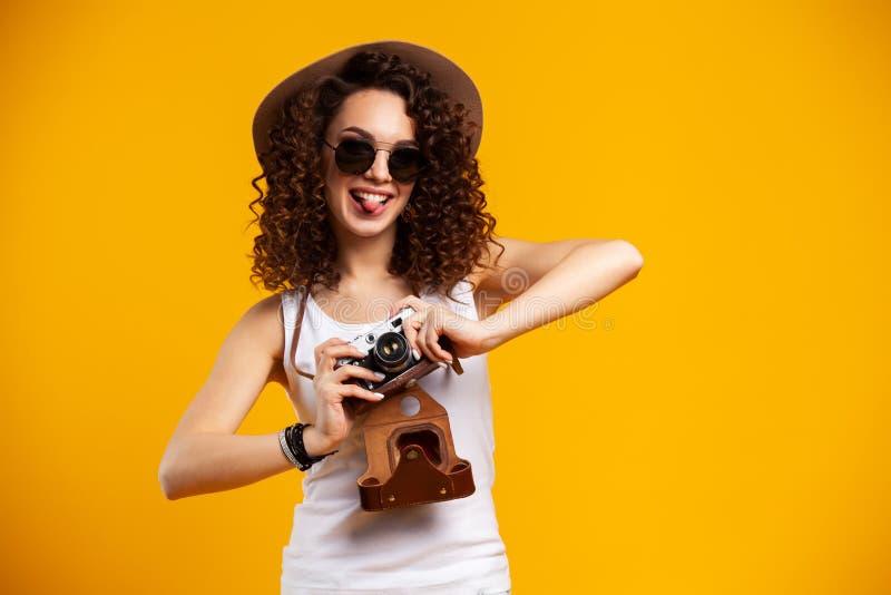 Het portret van lachende jonge vrouw in oogglazen die beelden op retro uitstekende fotocamera nemen isoleerde op heldere geel stock fotografie
