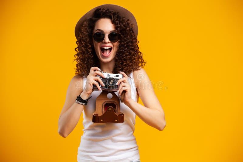 Het portret van lachende jonge vrouw in oogglazen die beelden op retro uitstekende fotocamera nemen isoleerde op heldere geel stock afbeelding