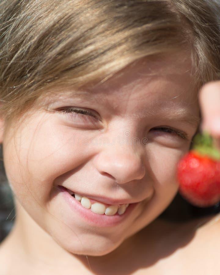 Het portret van leuk blonde Kaukasisch meisje houdt een rode bes in haar hand Het meisje glimlacht stock afbeelding