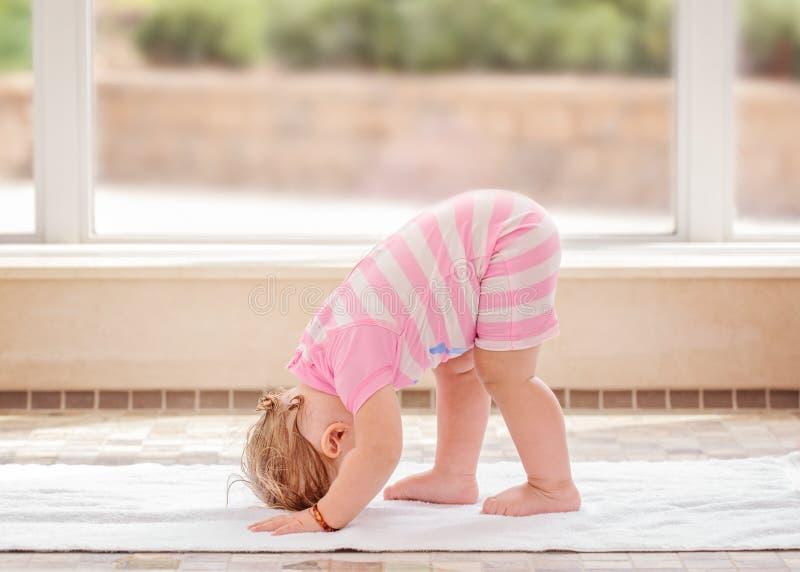 Het portret van leuk Kaukasisch babymeisje die fysieke geschiktheid doen oefent yoga op vloer uit stock foto's