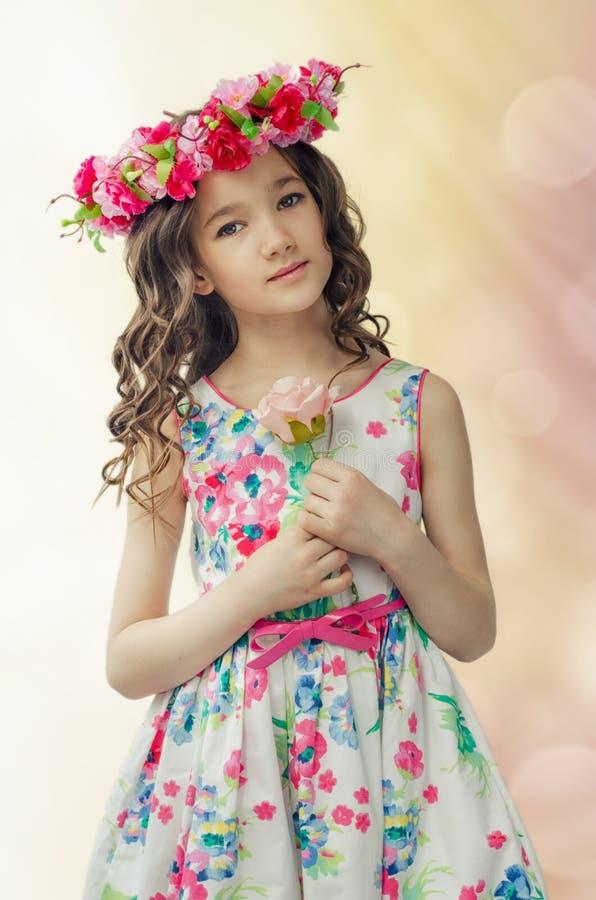 Het portret van leuk meisje in aardige de lentekleding, met bloemkroon op hoofd, houdt roze in handen toenam royalty-vrije stock foto's