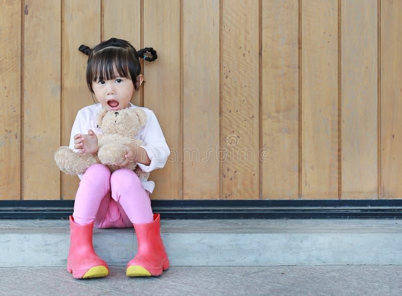 Het portret van leuk meisje zit en koesterend Teddy Bear tegen houten plankmuur stock fotografie