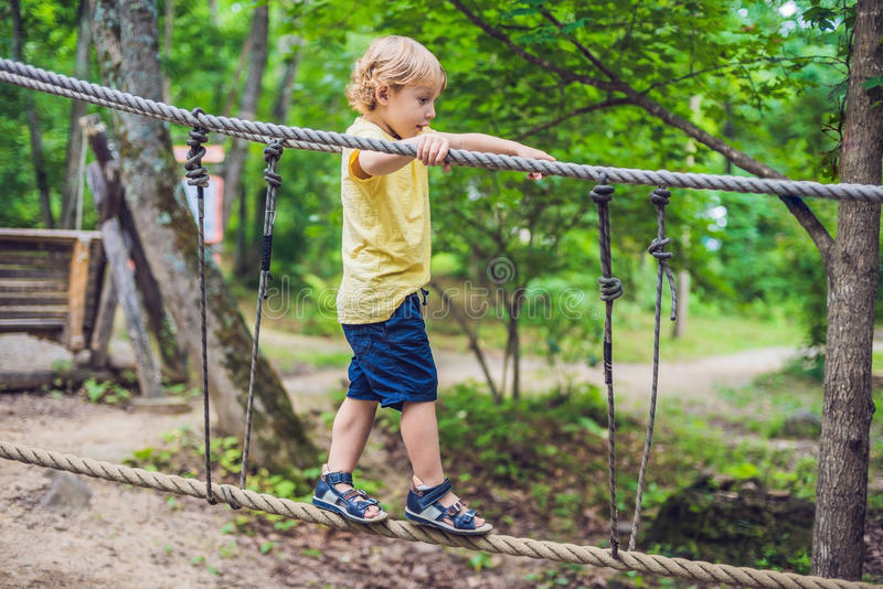 Het portret van leuk weinig jongen loopt op een kabelbrug in een adventu stock foto's