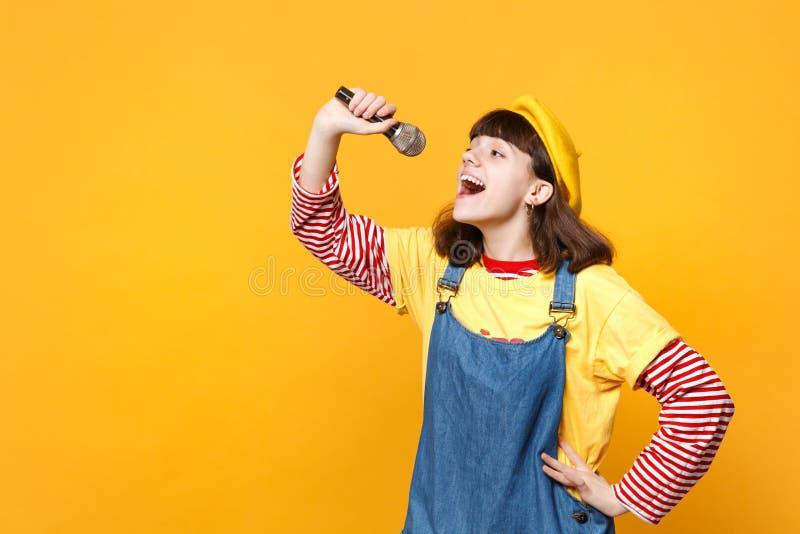 Het portret van leuke meisjestiener in Franse die baret en het denim sundress zingen lied in microfoon op gele muur wordt geïsole royalty-vrije stock afbeelding