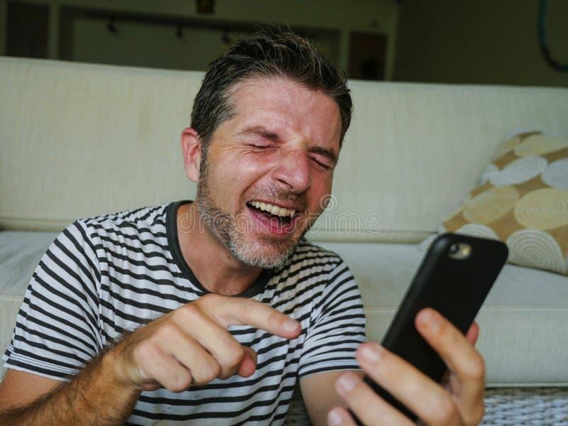 Het portret van het levensstijlhuis van de jonge gelukkige mens die als gekke gebruikende mobiele telefoon lachen die op iets let stock afbeelding