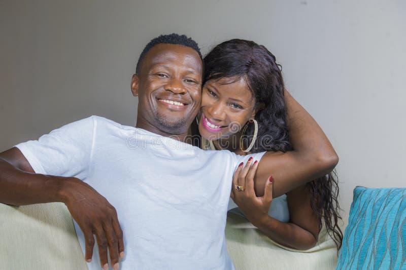 Het portret van het levensstijlhuis van jong gelukkig en succesvol romantisch Afrikaans Amerikaans paar in liefde ontspande comfo stock afbeelding