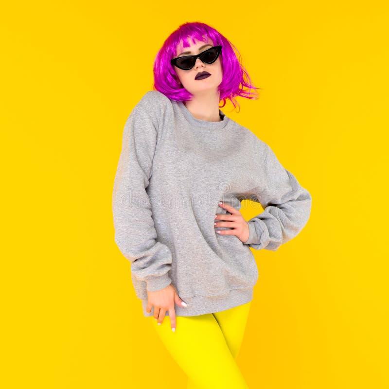 Het portret van het maniermeisje op gele achtergrond Gekke stijl jonge vrouw in roze pruik royalty-vrije stock foto's
