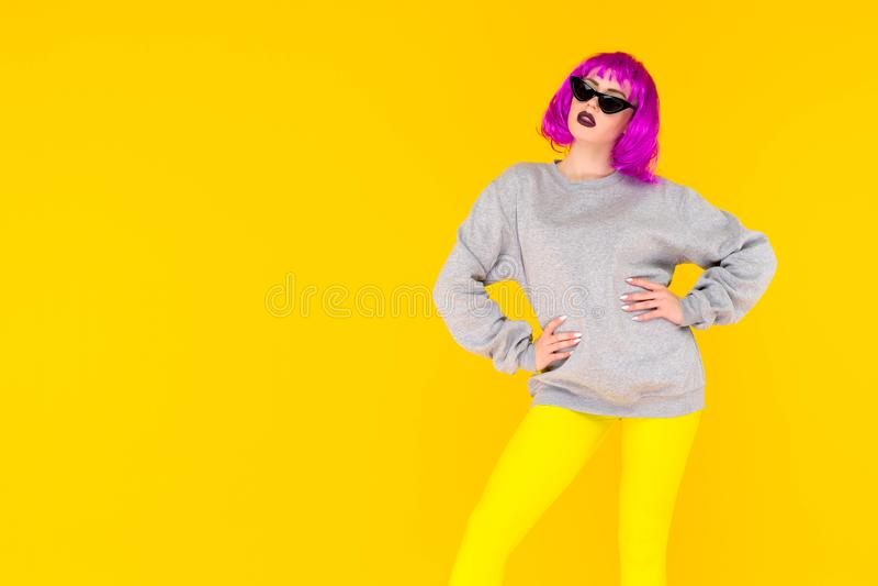 Het portret van het maniermeisje op gele achtergrond Gekke stijl jonge vrouw in roze pruik stock foto