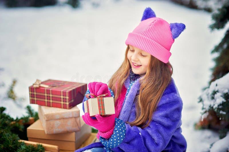 Het portret van meisje in de winter bosmeisje draagt een Kerstboom en stelt met slee voor stock fotografie