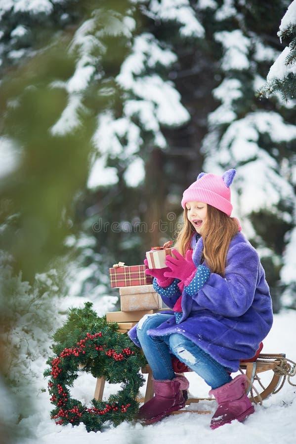Het portret van meisje in de winter bosmeisje draagt een Kerstboom en stelt met slee voor stock foto