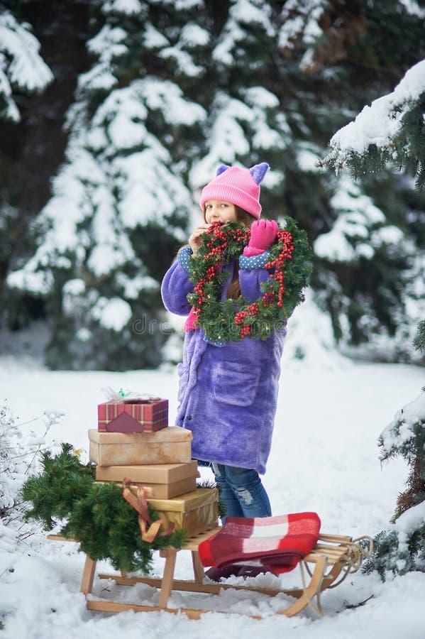Het portret van meisje in de winter bosmeisje draagt een Kerstboom en stelt met slee voor royalty-vrije stock fotografie