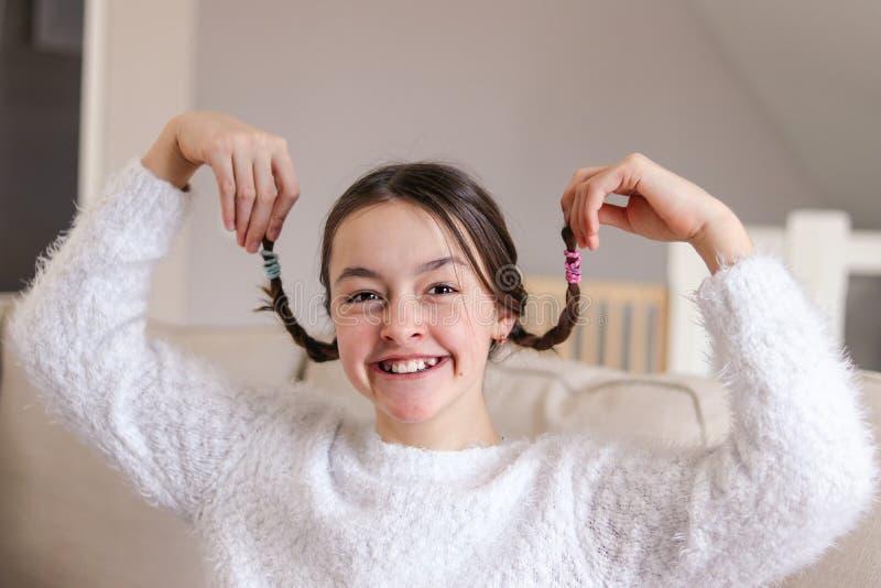 Het portret van het modieuze dwaze aantrekkelijke glimlachen preteen meisje die haar vlechten steunen en gezichten maken thuis zi royalty-vrije stock foto