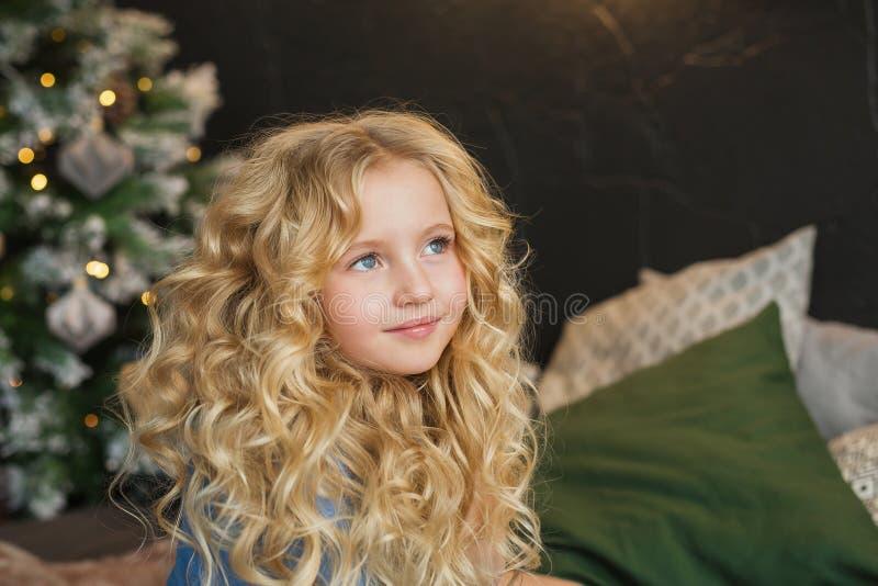 Het portret van mooi blondemeisje glimlacht en kijkt kant op een bed in Kerstmistijd stock afbeeldingen